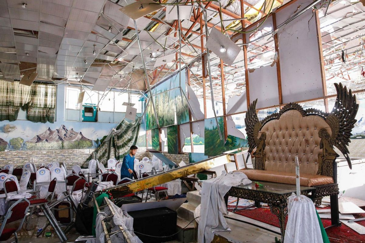 People survey the destruction after an overnight suicide bomb explosion that targeted a wedding reception in Kabul, Afghanistan, on Aug 18, 2019.