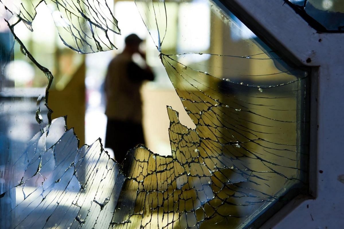 A man is seen through a broken window of a wedding hall after a deadly bomb blast in Kabul, Afghanistan, on Aug 18, 2019.