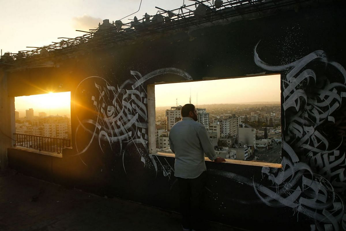 A Palestinian man gazes at Gaza City from a rooftop ornated with Arabic calligraphy on August 19, 2019. PHOTO:  AFP