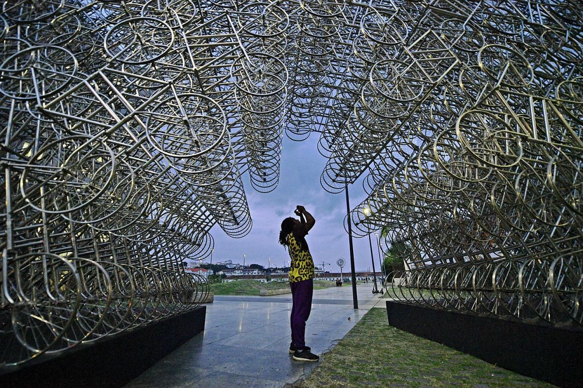 "A man takes a photo of an art installation entitled ""Forever Cycles"" by Chinese artist Ai Weiwei in Rio de Janeiro, Brazil, on August 19, 2019. PHOTO: AFP"