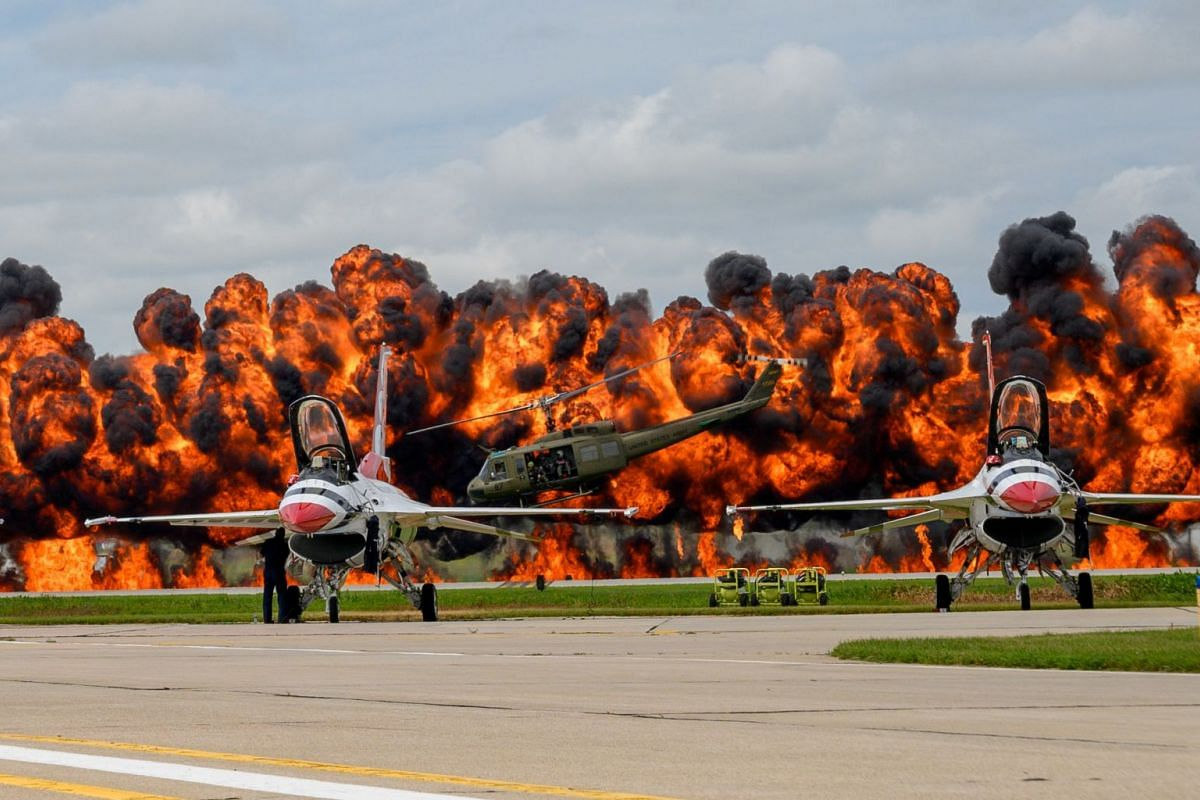 U.S. Air Force Thunderbirds sit on the tarmac while a helicopter picks up a downed pilot amid pyrotechnics simulation during a Vietnam War reenactment at the 2019 Sioux Falls Airshow in Sioux Falls, South Dakota, U.S. August 18, 2019. PHOTO: U.S. AIR