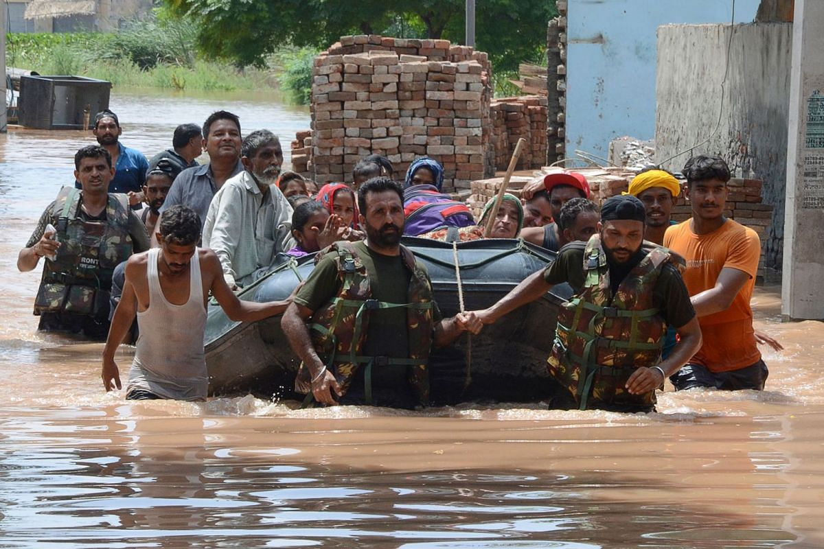Indian army personnel rescue local residents in a rubber boat following flooding waters in Kang Khurd, some 40 Km from Kapurthala on August 20, 2019. PHOTO: AFP
