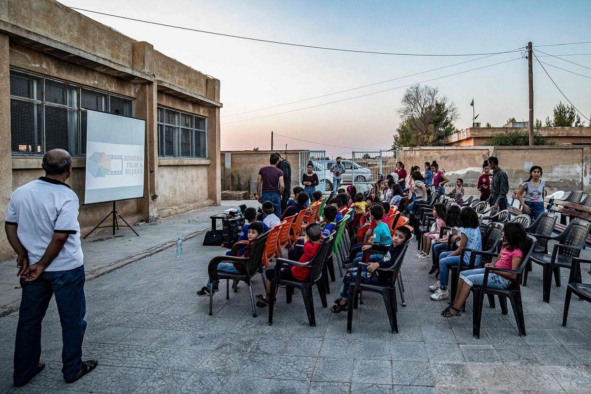 "A photo issued on August 20, 2019 shows children attending a film screening as part of the mobile cinema ""Komina Film"" initiative organised by Syrian-Kurdish filmmaker Shero Hinde, at a school yard in the village of Shaghir Bazar, 55 kilometres south"