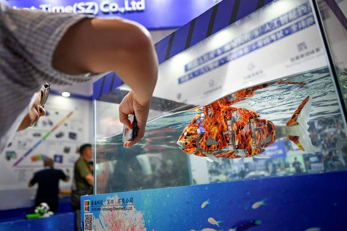 A visitor uses his mobile phone to take a picture of a robofish at the 2019 World Robot Conference in Beijing on August 20, 2019. PHOTO: AFP