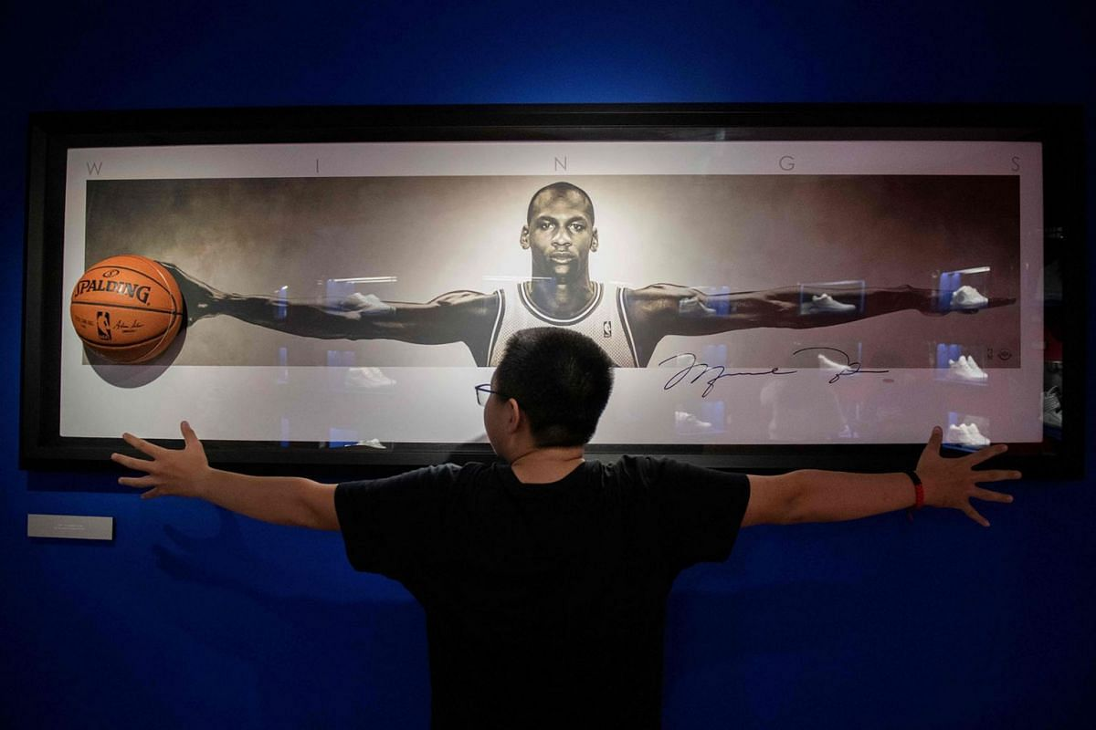 A visitor gestures in front of a picture of US basketball player Michael Jordan at the NBA exhibition in Beijing on August 19, 2019. The Basketball world cup will be held from August 31 to September 15 2019 in China. PHOTO: AFP