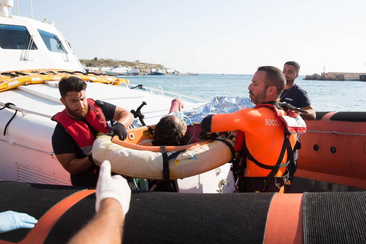 A woman being evacuated by members of the Italian Coast Guard from the rescue ship Open Arms.