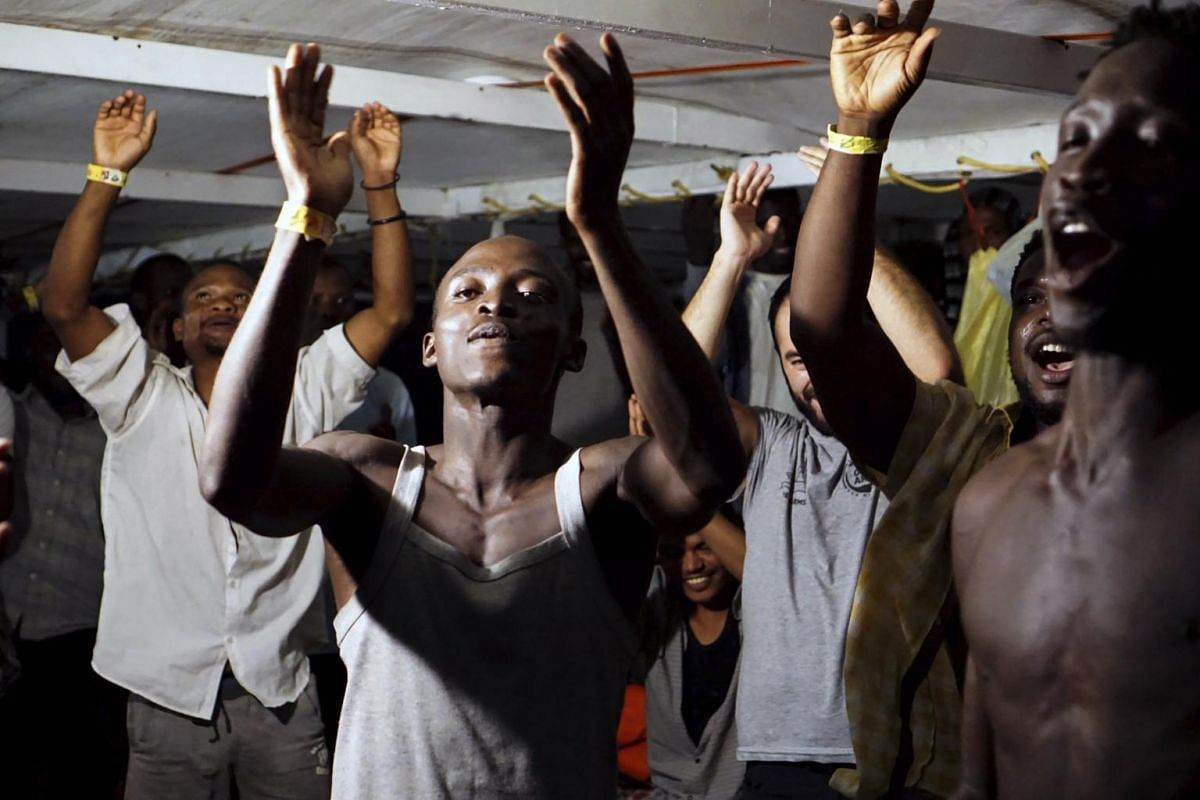 Migrants onboard charity vessel Open Arms celebrate the news that Italian authorities have ordered that they be disembarked on the island of Lampedusa in southern Italy, on Aug 20, 2019.