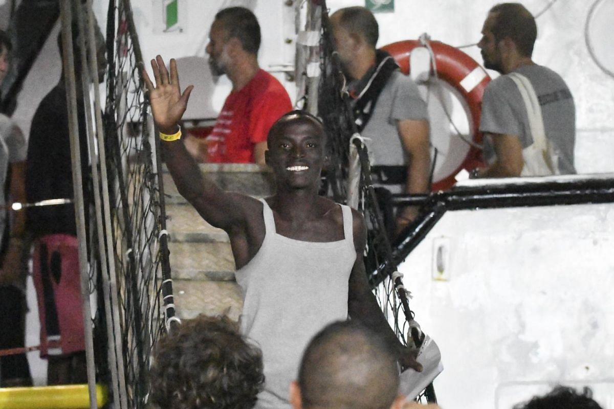 A migrant leaving the Open Arms rescue ship.