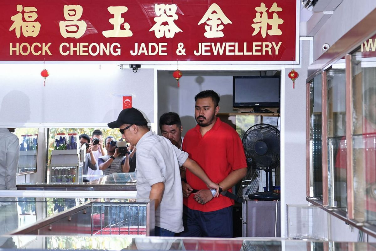 One of the three alleged Ang Mo Kio jewellery shop robbers was brought back to the crime scene on August 21, 2019. PHOTO: THE STRAITS TIMES/DESMOND FOO