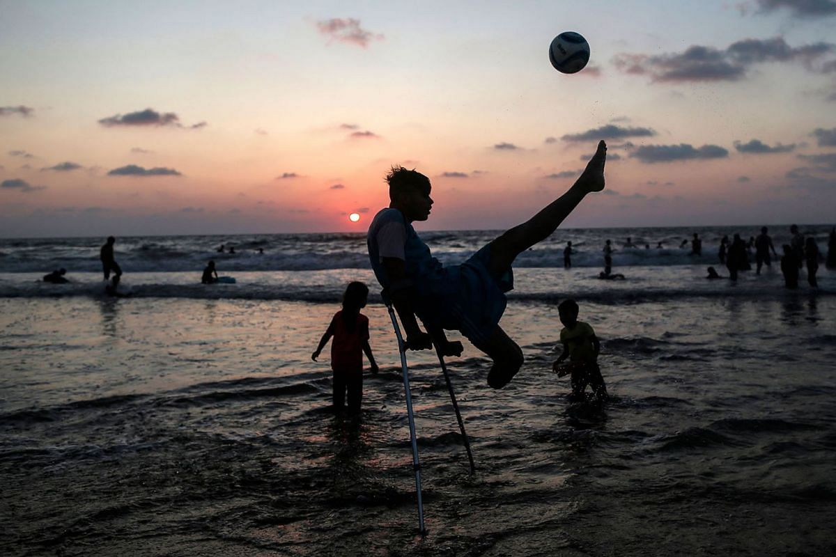 Palestinian amputees Mohammed Eliwa, 17, who lost his leg during clashes on the border with Israel, plays football on the beach in Gaza City on August 20, 2019. PHOTO: AFP