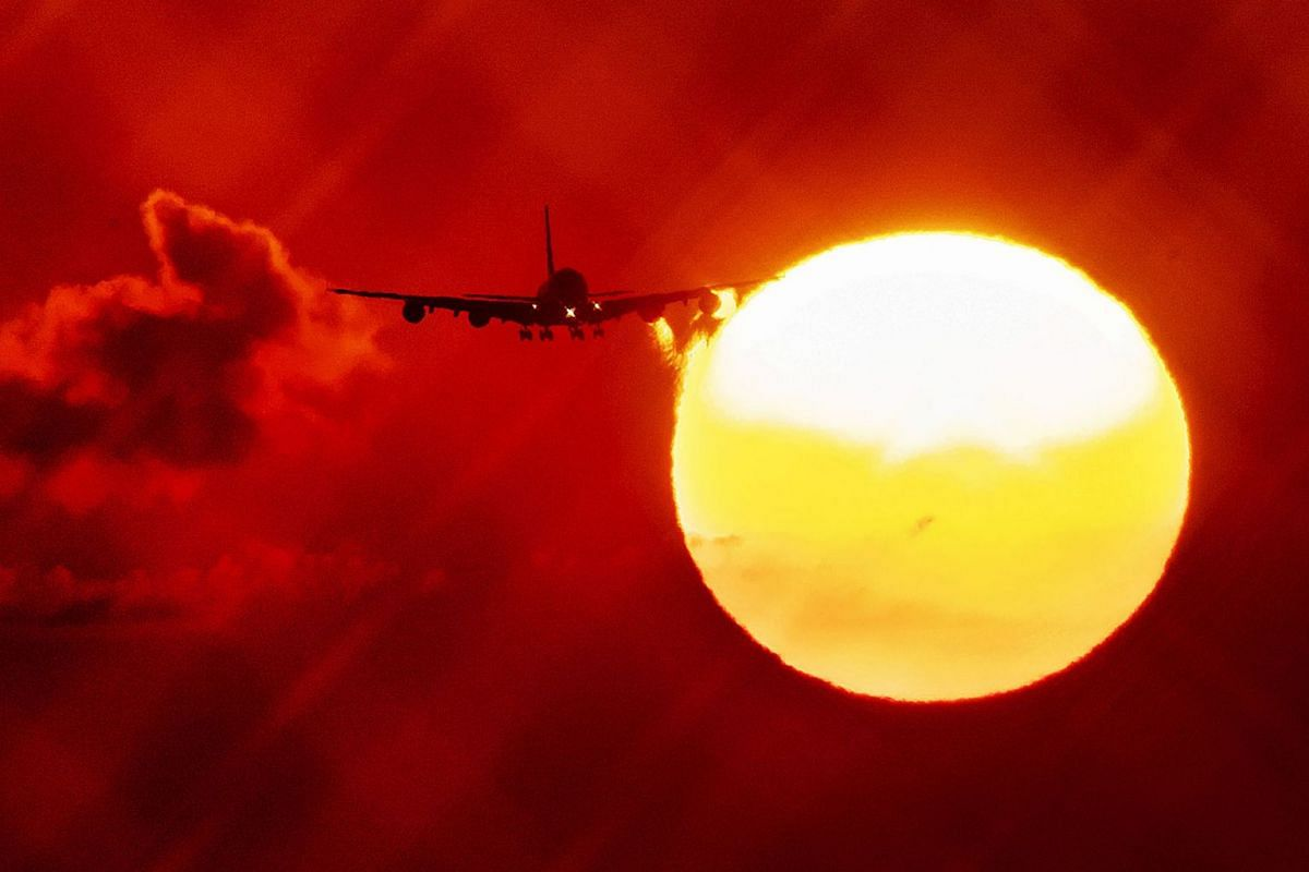 An aircraft passes the rising sun as it approaches the airport in Frankfurt, Germany, Wednesday, August  21, 2019. PHOTO: AP