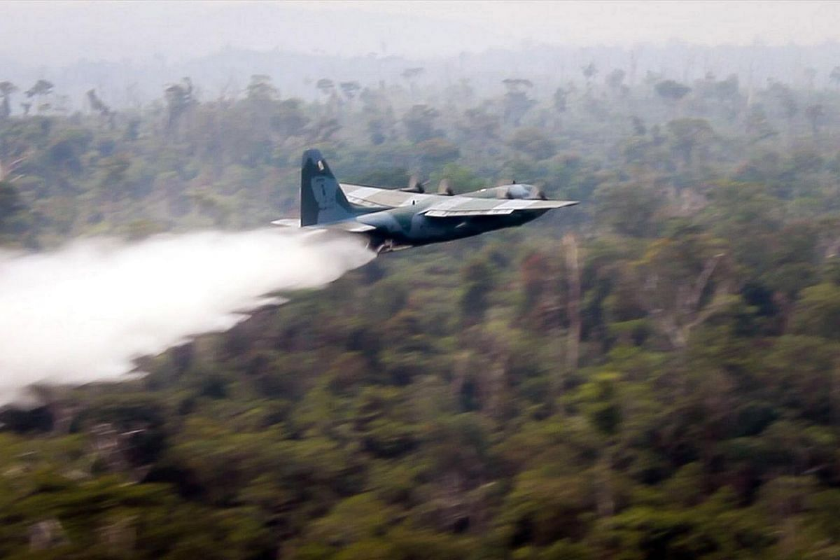 """A handout photo made available by the """"Agencia Brasil"""" shows a Hercules C-130 plane of Brazil's Air Force dropping water to fight the fire at the Amazon forest in Rondonia state, Brazil, on Aug 25, 2019."""