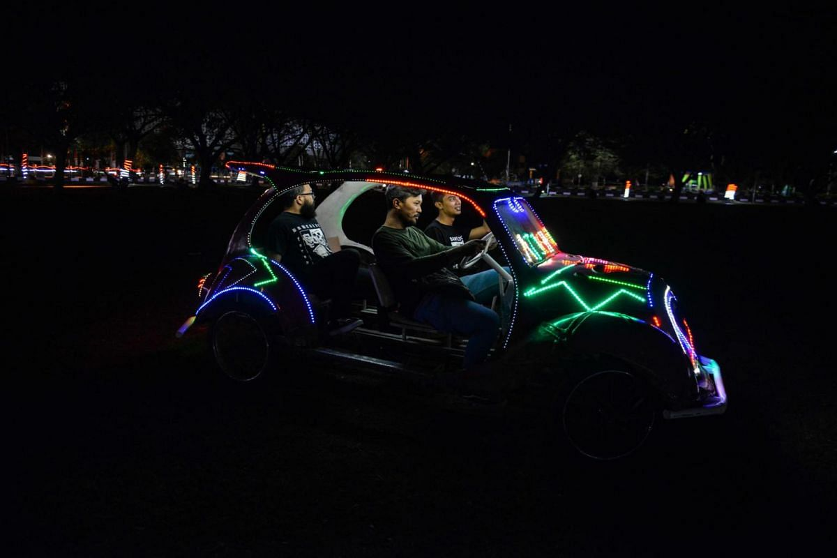 Young people ride a pedal-powered vehicle decorated with colourful lights at a playground in Banda Aceh, Indonesia, on Aug 25, 2019.