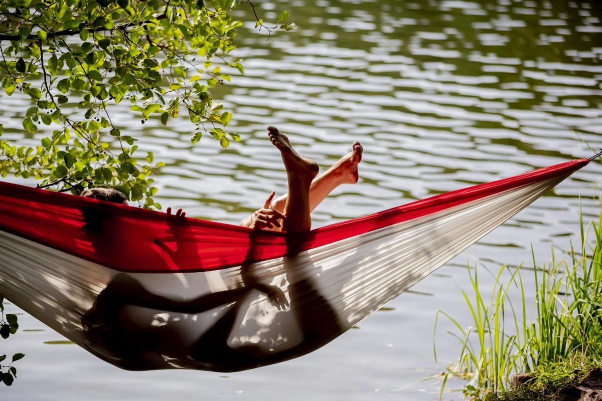 A couple enjoys the warm late summer weather in a hammock in Berlin, Germany on Aug 28, 2019.