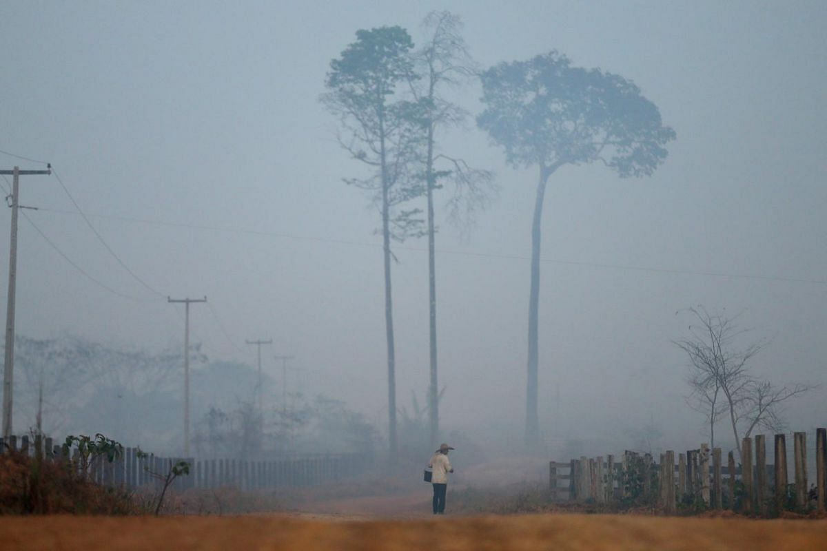 A man walks amid smoke from a burning tract of Amazon jungle as it is cleared by loggers and farmers near Porto Velho, Brazil on Aug 28, 2019.