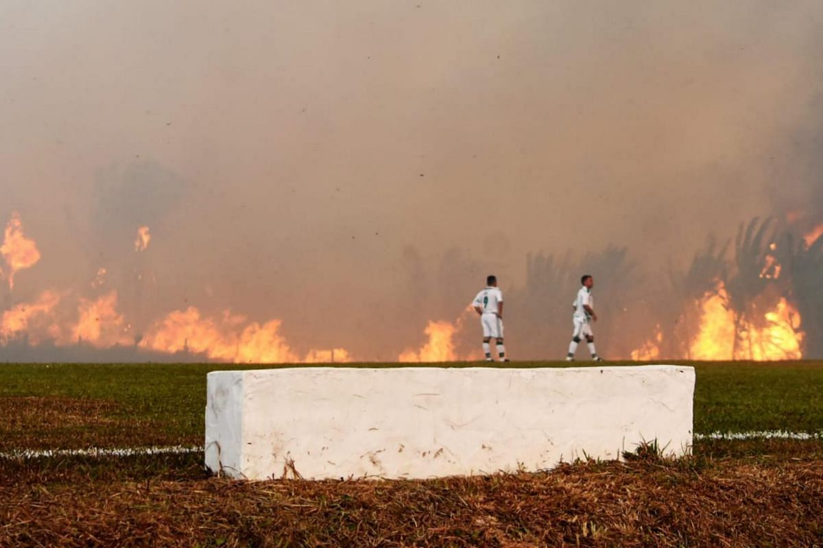 A wildfire interrupts a third division football match between Atletico Acreano and Luverdense, at Antonio Aquino Lopes stadium in Rio Branco, Brazil on Aug 25, 2019.