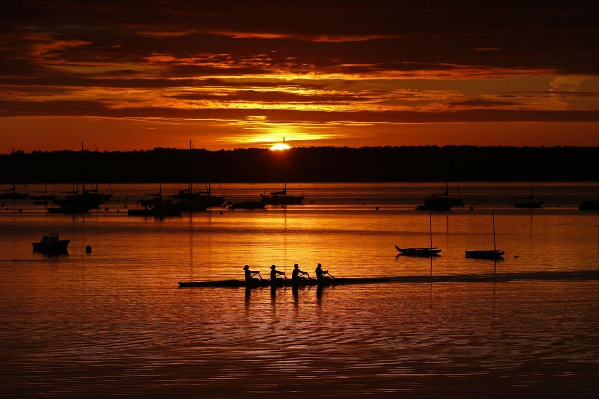 A quad scull of rowers begins their workout in Casco Bay as the sun starts to peak over Great Diamond Island in Portland, Maine on Aug 28, 2019.