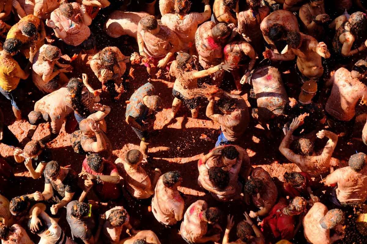 Revellers paint the town red with tomato pulp during the annual La Tomatina food fight festival in Bunol, near Valencia, Spain, on Aug 28, 2019.