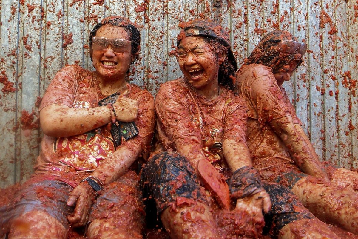 Revellers are pelted with tomatoes during the annual La Tomatina tomato fight fiesta, in the village of Bunol, near Valencia, Spain, on Aug 28, 2019.