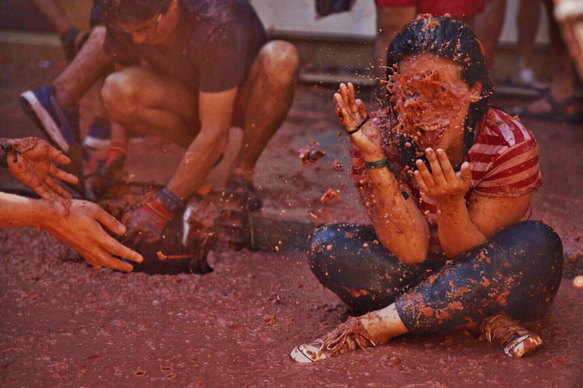 A participant splashes in the remains of tomatoes during the La Tomatina festival, the world's biggest food fight.