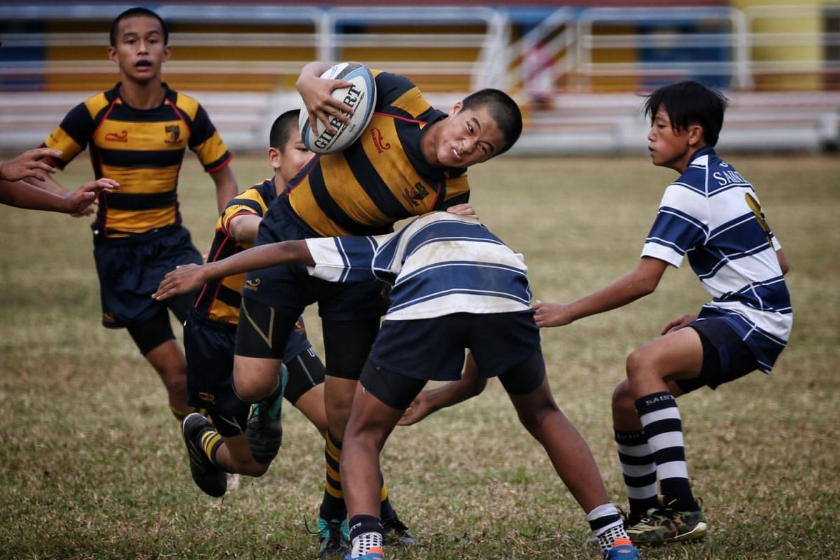 Ryan Seow of ACS(I) is challenged by St Andrew's players in the Boys' C Division rugby finals at Queenstown Stadium on Aug 29, 2019.
