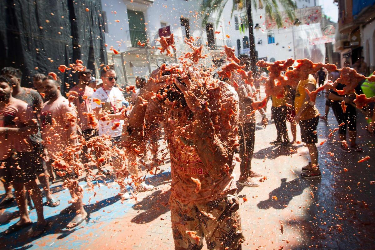 A reveller is pelted with tomato pulp at the annual La Tomatina festival in the eastern Spanish town of Bunol, on Aug 28, 2019.
