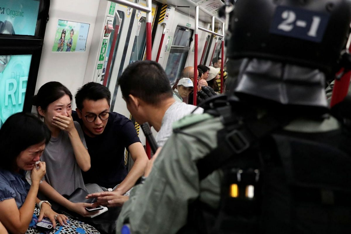 Commuters react as police officers looking for protestors raid a metro train, in Hong Kong, China September 1, 2019. PHOTO: REUTERS