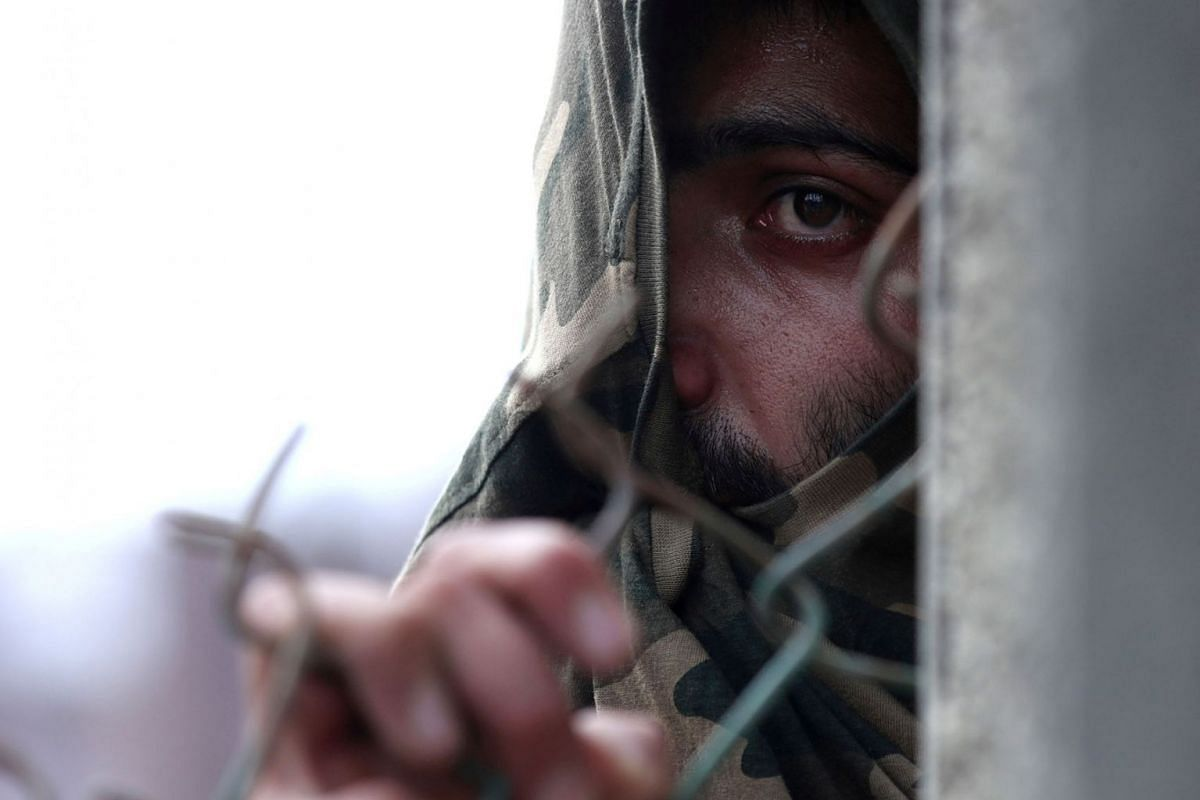 A Kashmiri man takes cover behind a barricade during clashes with Indian security forces after scrapping of the special constitutional status for Kashmir by the Indian government, in Srinagar, India, August 30, 2019. PHOTO: REUTERS