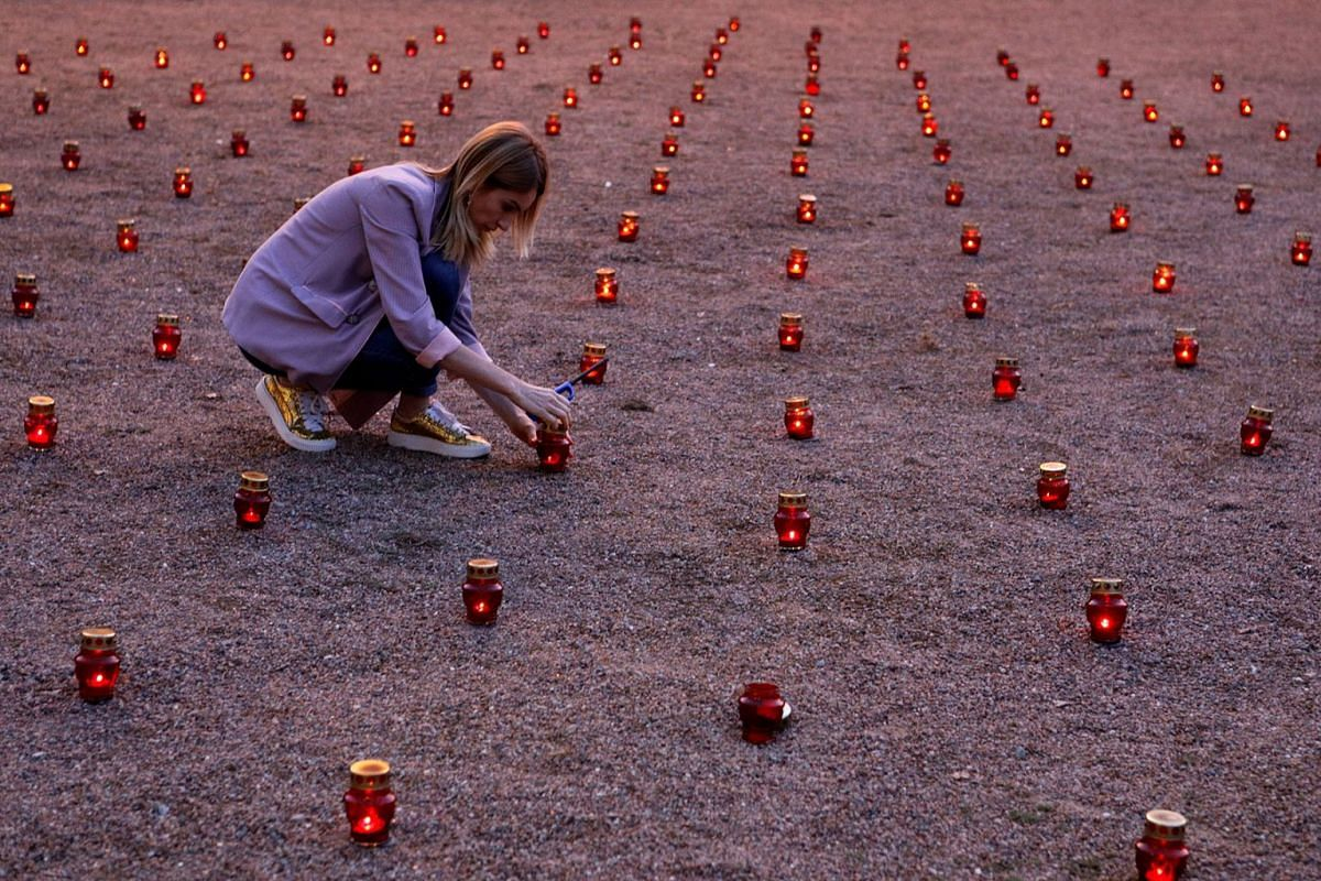 A woman lights candles during a memorial ceremony marking the 15th anniversary of the deadly school siege in the town of Beslan, Russia, September 1, 2019. PHOTO: REUTERS