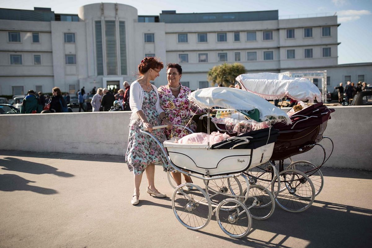 Two women dressed in period outfits push vintage prams past the Art Deco-styled Midland Hotel during the Vintage By The Sea festival in Morecambe, north-west England on September 1, 2019. PHOTO: AFP