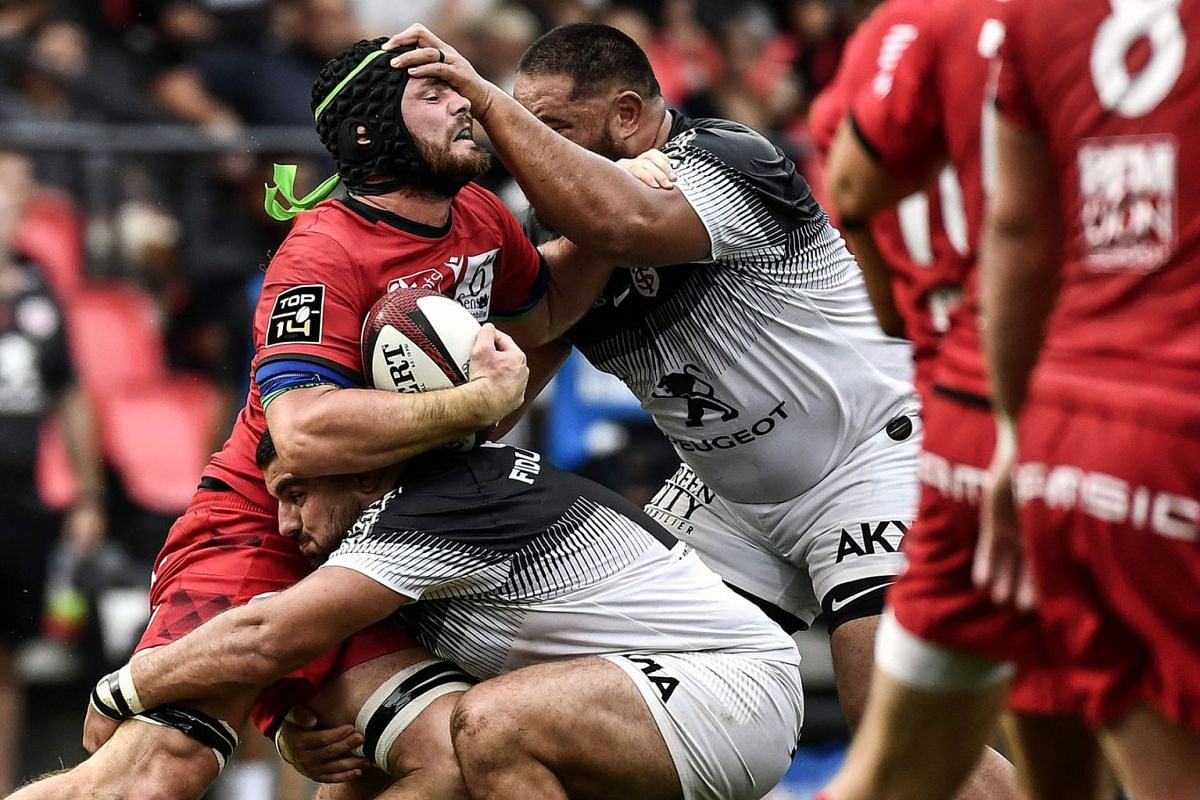 Lyon's Australian flanker Liam Gill (left) is tackled by Toulouse's French prop Clement Castets (bottom) and Toulouse's New Zealand prop Charlie Faumuina (right) during the French Top 14 rugby union match between Lyon (LOU) and Toulouse (ST) on Septe