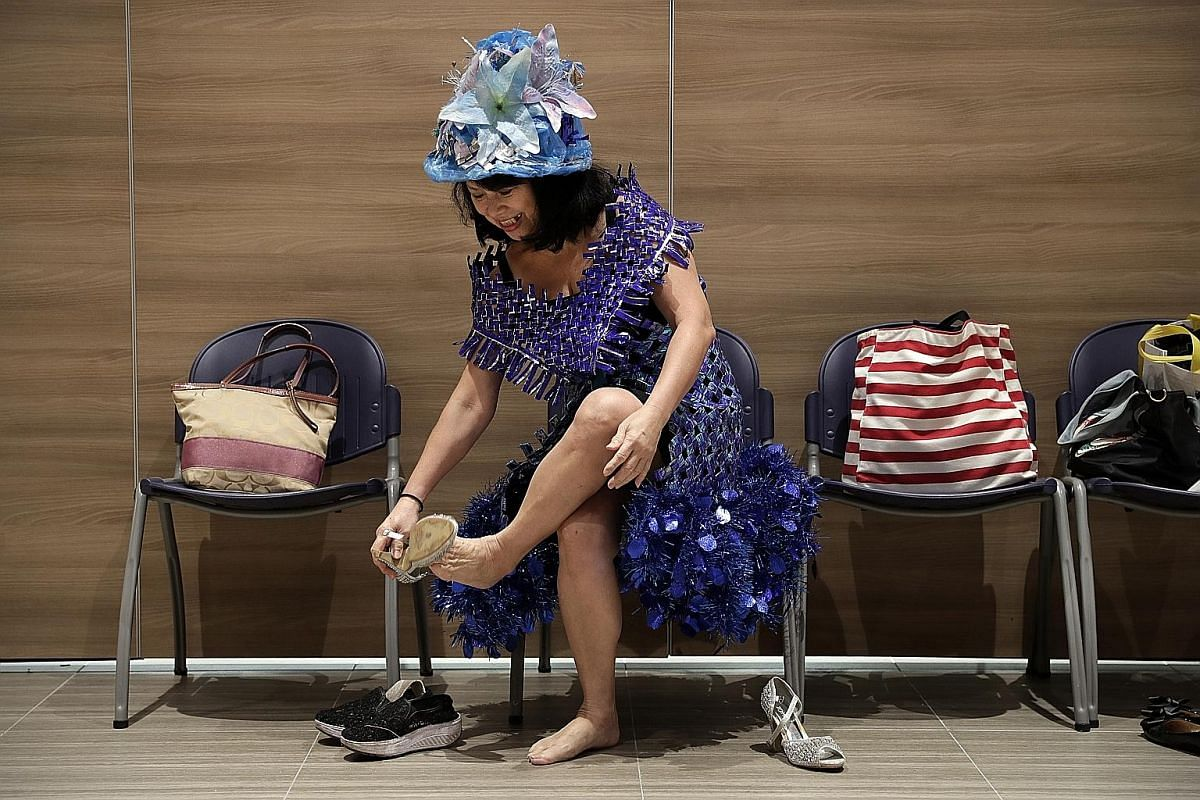 Madam Annie Phua getting ready for a rehearsal. Her blue outfit is woven together from empty packets of Oreo biscuits she had eaten and the hem is lined with leftover Christmas decorations from her home.