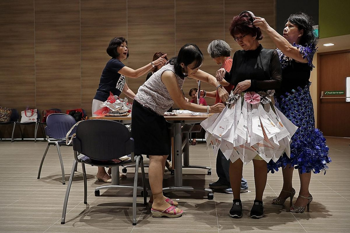 Housewife Lilian Lim (second from right) in a dress constructed from photocopying paper packaging. The packaging is folded and then stapled together to form the pleats of the dress. Madam Lim collected the packaging from a relative who works at a bookstor