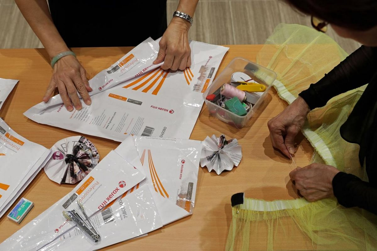 Madam Lilian Lim (right), a housewife, works on her dress with the help of another group member as they put together a dress made from the photocopying paper packaging that she collected from a relative who works at a bookstore. The packaging is fold