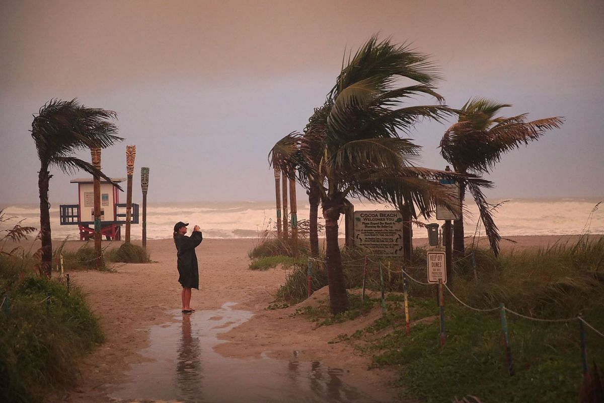 A woman takes a picture as the effects of Hurricane Dorian begin to be felt on September 2, 2019 in Cocoa Beach, Florida. Dorian, once expected to make landfall near Cocoa Beach as a category 4 storm, is currently predicted to turn north and stay off
