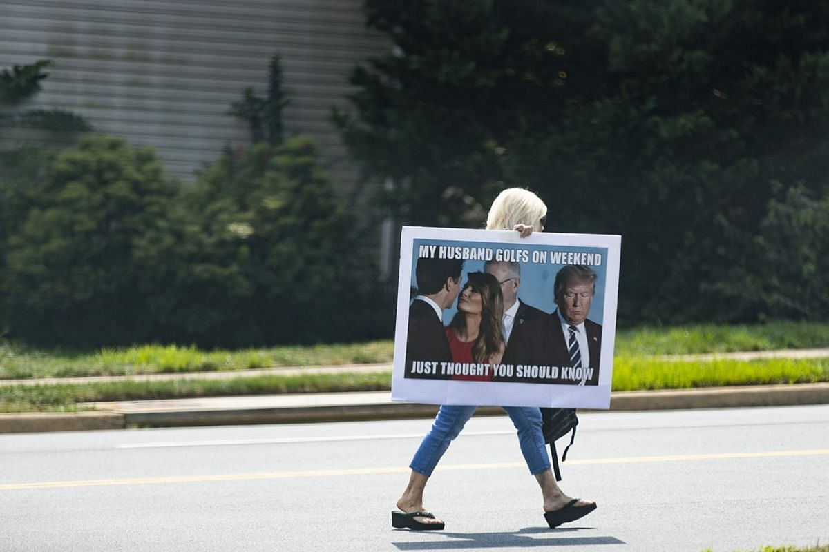 A protester with a sign outside the Trump National Golf Club during President Donald Trump's visit in Sterling, Va., Sept. 2, 2019. PHOTO: THE NEW YORK TIMES