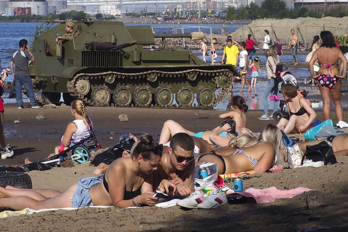 People sunbath after the World War II battle reconstruction held by members of historical military clubs at the Finnish Gulf coast in St.Petersburg, Russia, Sunday, Sept. 1, 2019, with a World War II ages artillery vehicle in background. PHOTO: AP