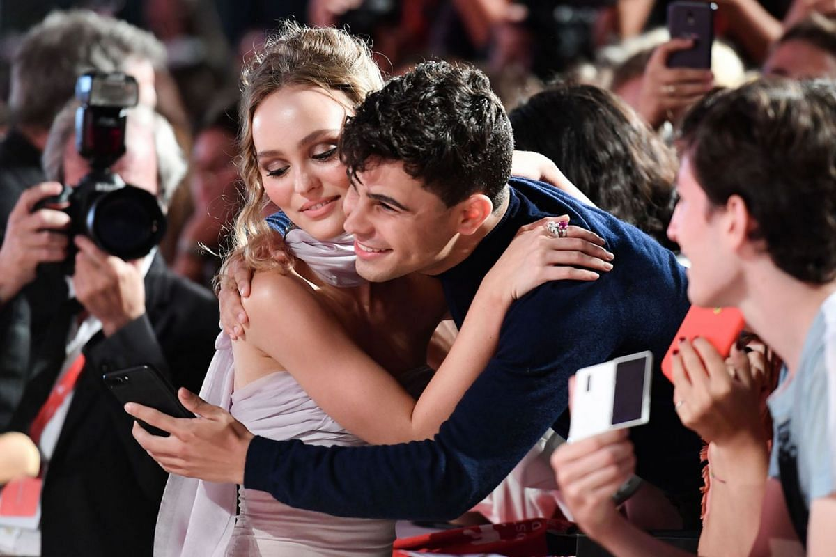 """French US actress Lily-Rose Depp (L) embraces a fan and poses for a selfie photo as she arrives for the screening of the film """"The King"""" presented out of competition on September 2, 2019 during the 76th Venice Film Festival at Venice Lido. PHOTO: AFP"""