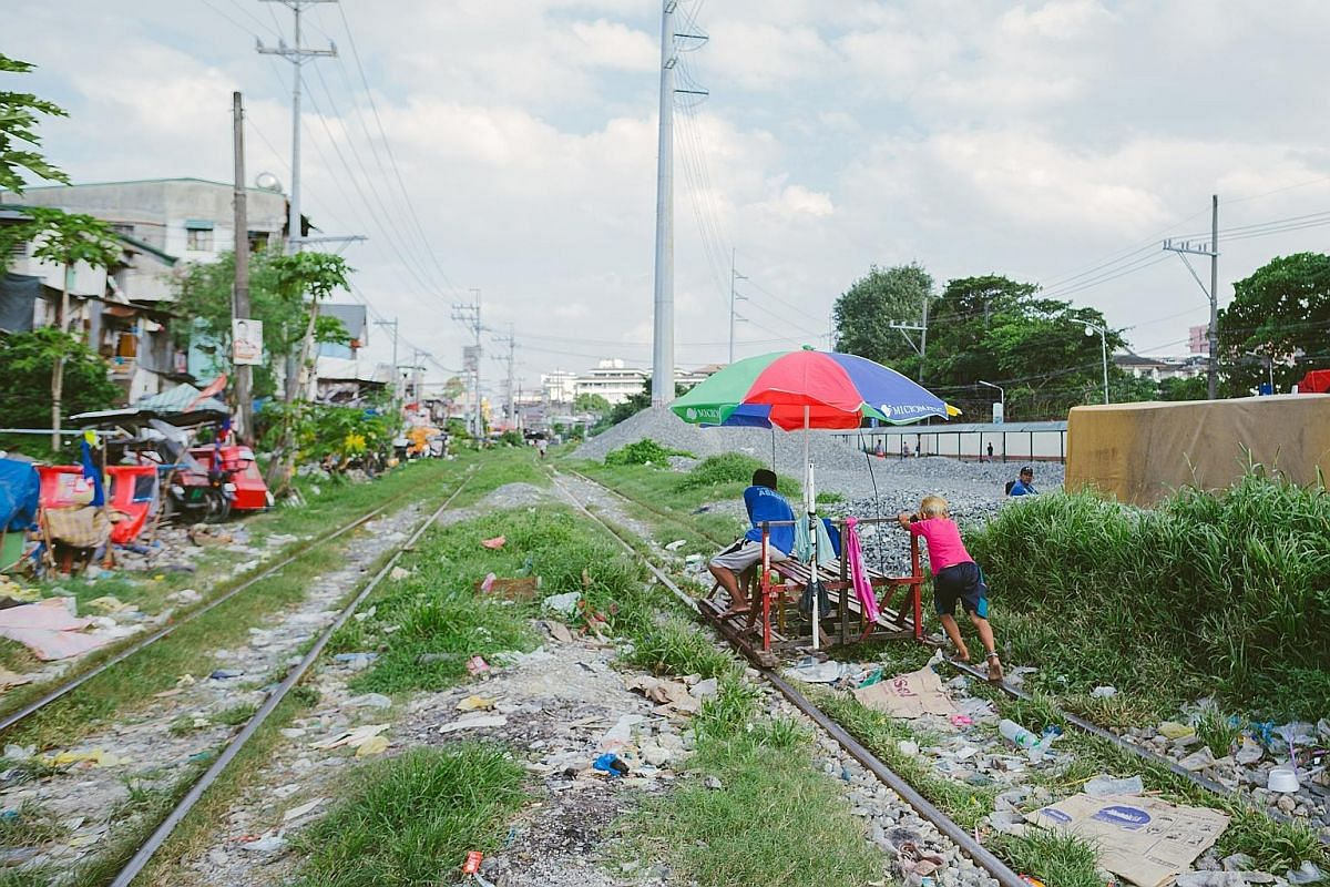 Commuters on a trolley being pushed along a rail line in Manila's Sta Mesa district. It is a risky commute but saves them up to an hour in travelling time.