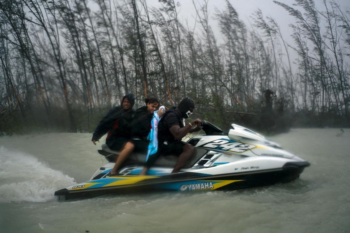 A woman trapped by flood waters during Hurricane Dorian is transported out of the area by volunteers on a jet ski near the Causarina bridge in Freeport, Grand Bahama, Bahamas, on Sept 3, 2019.
