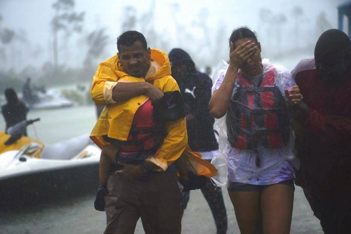 A family is escorted to a safe zone as Hurricane Dorian continues to rain in Freeport, Bahamas, on Sept 3, 2019.