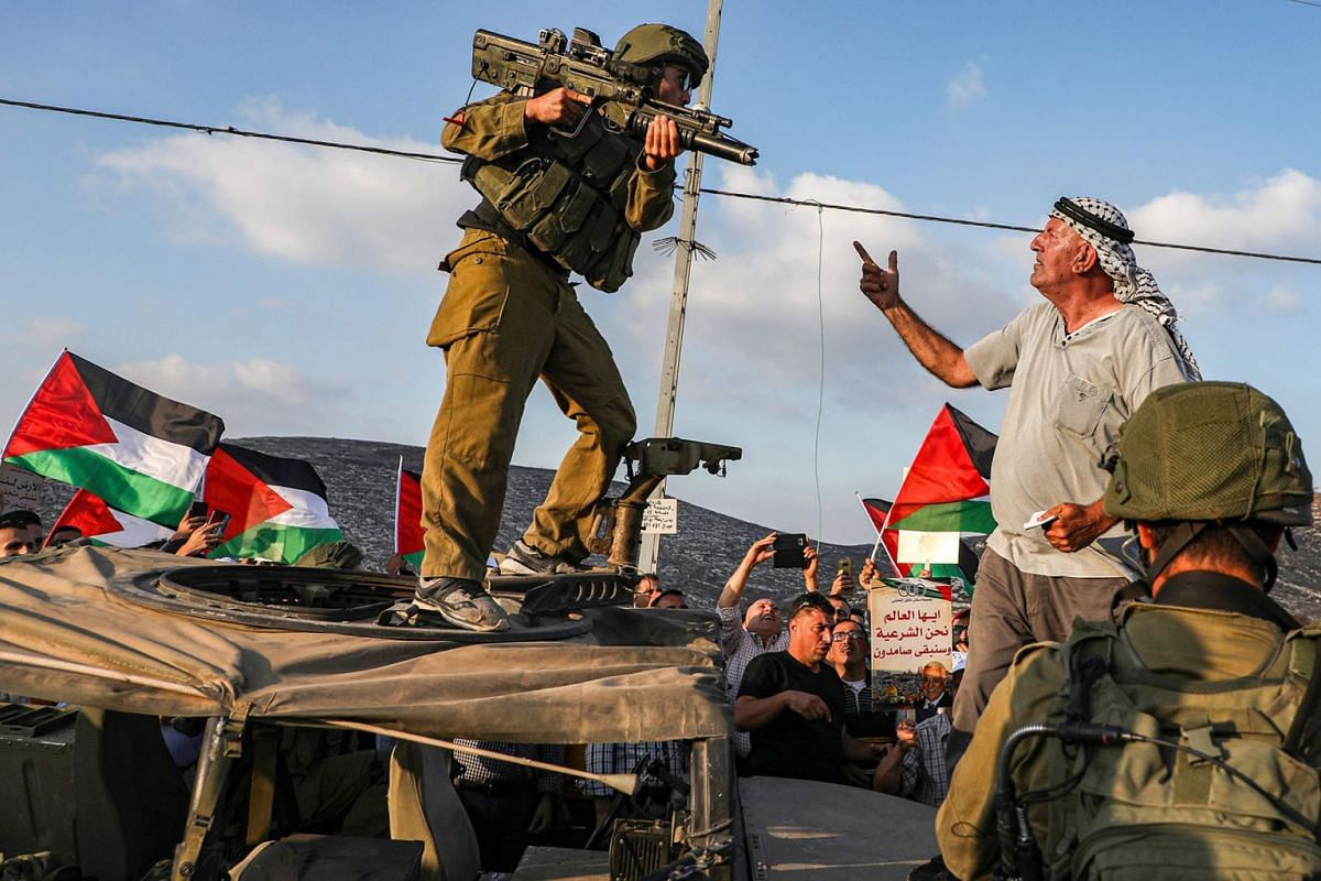 A Palestinian protester yells at an Israeli soldier as he confronts him atop an Israeli army vehicle during a protest against Israeli forces conducting an exercise in a residential area near the Palestinian village of Naqura, northwest of Nablus in t