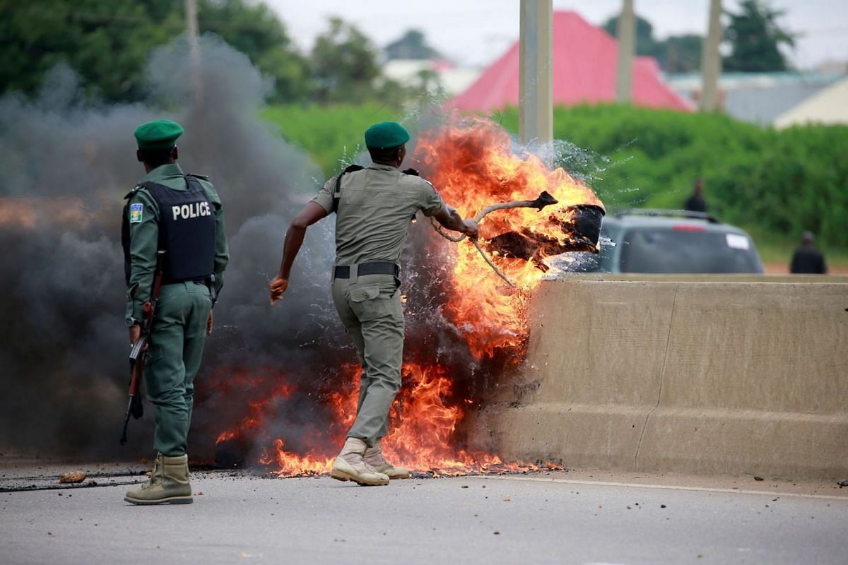 A police office removes burning tires from the road, as protesters set up fires to block traffic along Airport Road in Abuja, Nigeria September 4, 2019. PHOTO: REUTERS