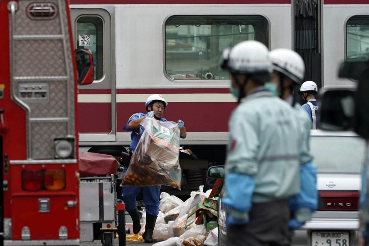 A police officer carries debris from the scene where a train sits derailed after its collision with a truck in Yokohama, south of Tokyo, on Sept 5, 2019.