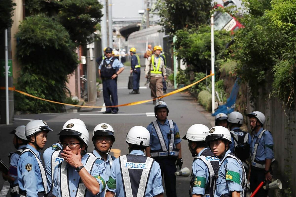 Japanese police officers gather at the scene where a train and a truck collided at a crossing in Yokohama, Kanagawa Prefecture on Sept 5, 2019.