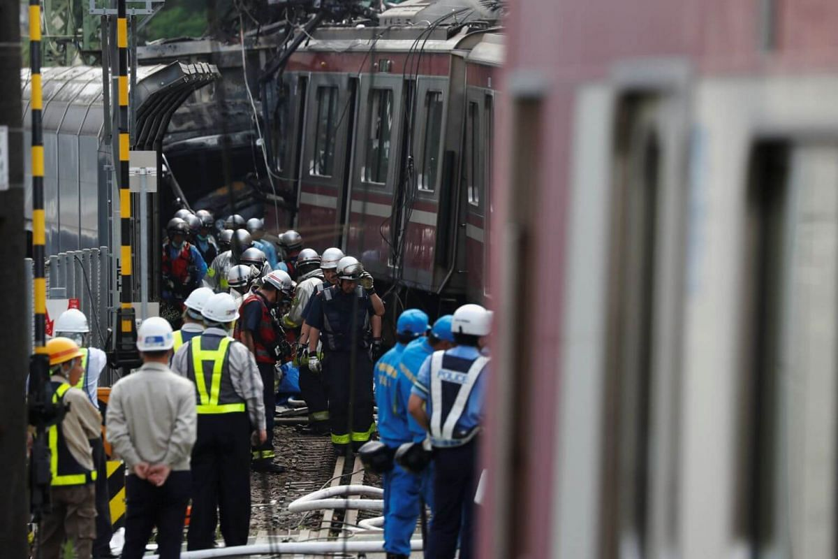A burned truck and derailed train are seen as rescue officers, police and railway company employees work at the scene after the collision in Yokohama, near Tokyo, Japan, on Sept 5, 2019.