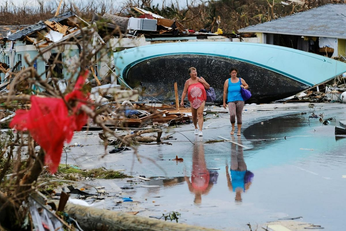 Women walk through the rubble in the aftermath of Hurricane Dorian on the Great Abaco island town of Marsh Harbour, Bahamas, on Sept 3, 2019.