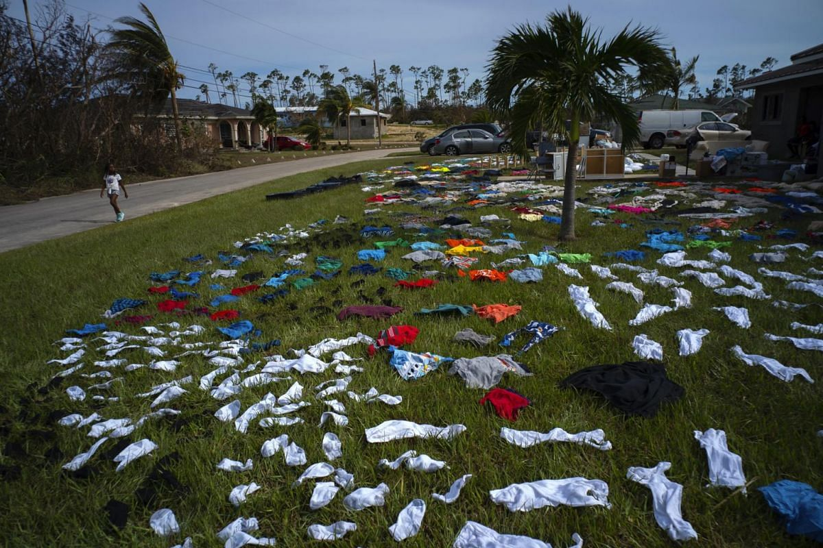 A child walks past clothes laid out to dry on a field in the aftermath of Hurricane Dorian, in the Arden Forest neighborhood of Freeport, Bahamas, on Sept 4, 2019.