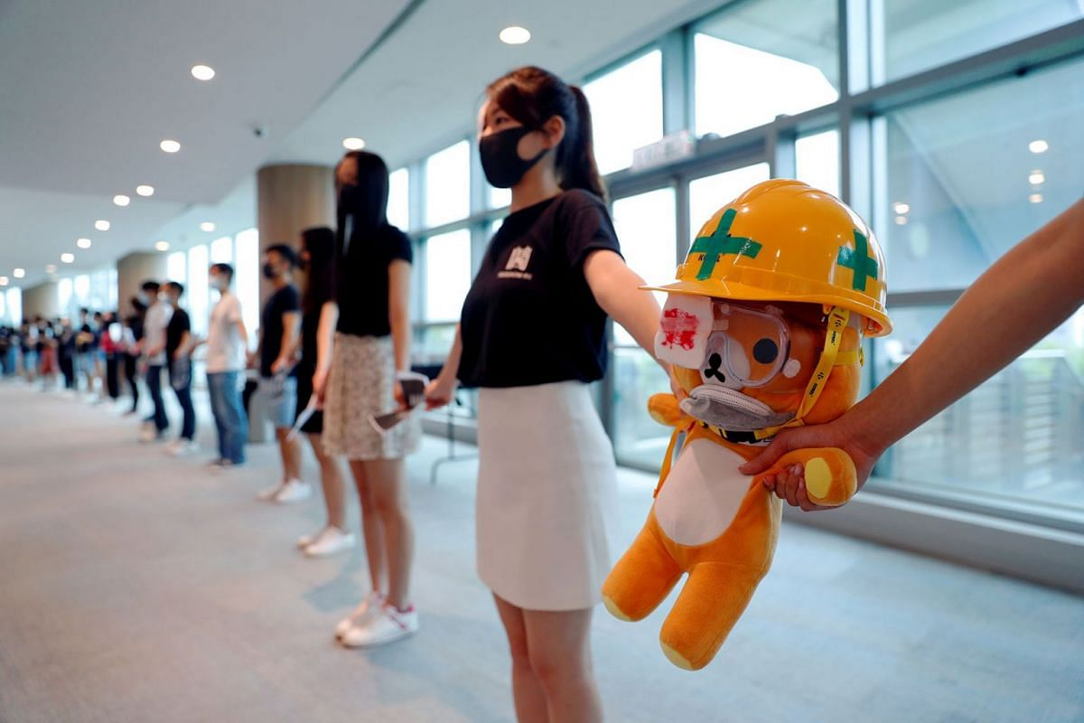 Medical students hold a stuffed doll with its eye covered as they form a human chain during a protest against the police brutality at the Faculty of Medicine in The University of Hong Kong, China, September 5, 2019. PHOTO: REUTERS