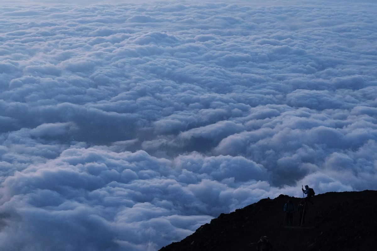 A photo issued on September 5, 2019, shows a climber stopping to take pictures of clouds while climbing towards the summit of Mount Fuji to watch the sunrise, August 27, 2019, in Japan. PHOTO: AP